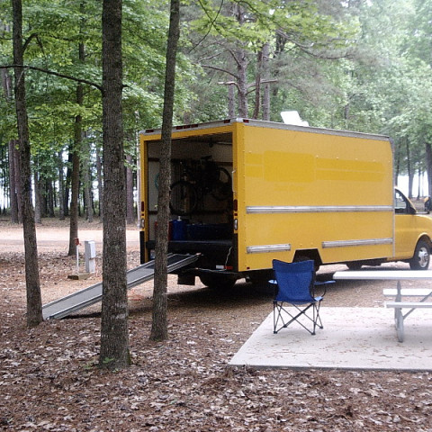 GMC CubeVan Stealth Camper set up in a campground