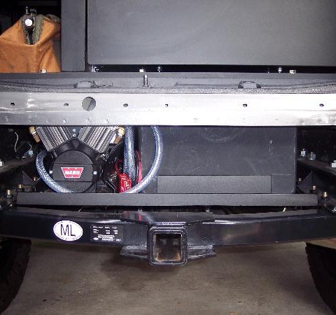 This is a picture from the rear of the van, where the spare tire used to be mounted. Since Vanaconda was on 35 and 37 inch tires, the spare wouldn't fit here anymore. Instead, UJoint Offroad created a storage area for a 12 gallon water tank and a 12 volt warn air compressor.