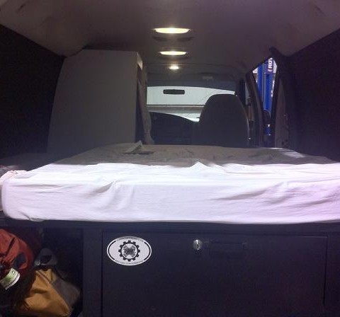 Vanaconda Van interior with a bed platform, locking storage drawer and ample storage for sleeping bags and other tool bags beside it still.